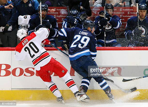 Sebastian Aho of the Carolina Hurricanes collides with Patrik Laine of the Winnipeg Jets along the boards during third period action at the MTS...