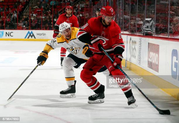 Sebastian Aho of the Carolina Hurricanes controls the puck ahead of Nick Bonino of the Nashville Predators during an NHL game on November 26 2017 at...