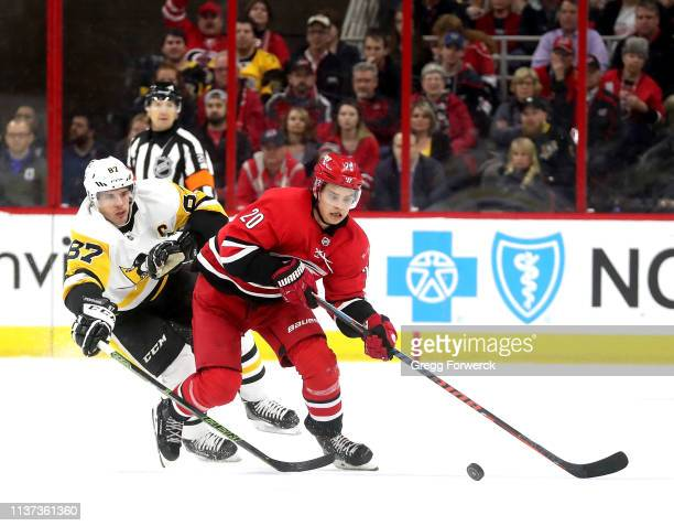 Sebastian Aho of the Carolina Hurricanes controls the puck away from the defense of Sidney Crosby of the Pittsburgh Penguins during an NHL game on...