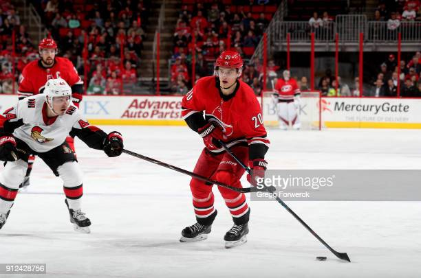 Sebastian Aho of the Carolina Hurricanes controls the puck away from the defense of JeanGabriel Pageau of the Ottawa Senators during an NHL game on...