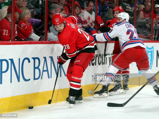 Sebastian Aho of the Carolina Hurricanes defends the puck along the end boards during an NHL game against the New York Rangers on March 31 2018 at...