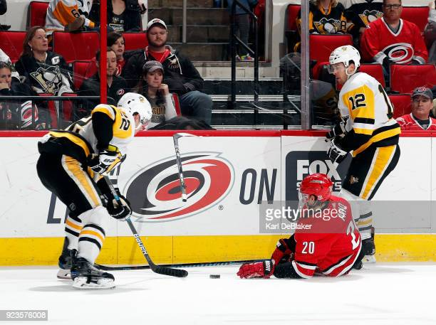 Sebastian Aho of the Carolina Hurricanes draws a tripping penalty from Dominik Simon of the Pittsburgh Penguins during an NHL game on February 23...