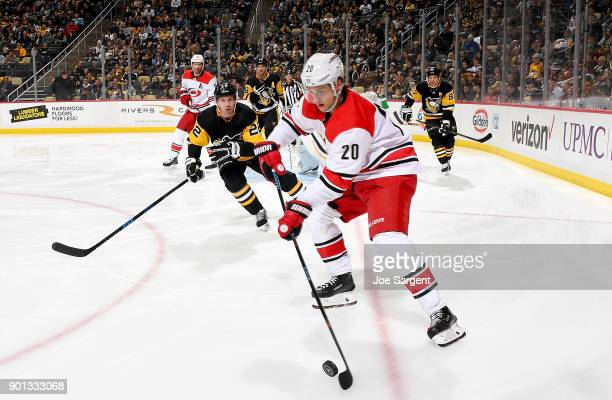 Sebastian Aho of the Carolina Hurricanes handles the puck against Matt Hunwick of the Pittsburgh Penguins at PPG Paints Arena on January 4 2018 in...