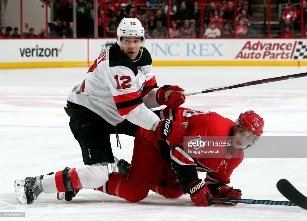 Sebastian Aho #20 of the Carolina Hurricanes is checked by Ben Lovejoy #12 of the New Jersey Devils during an NHL game on February 18, 2018 at PNC Arena in Raleigh, North Carolina.