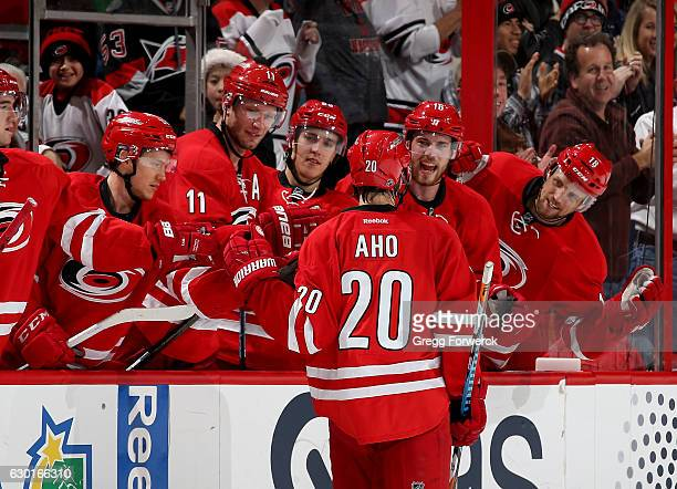 Sebastian Aho of the Carolina Hurricanes is congratulated by teammates after scoring in a shootout during an NHL game against the Buffalo Sabres on...