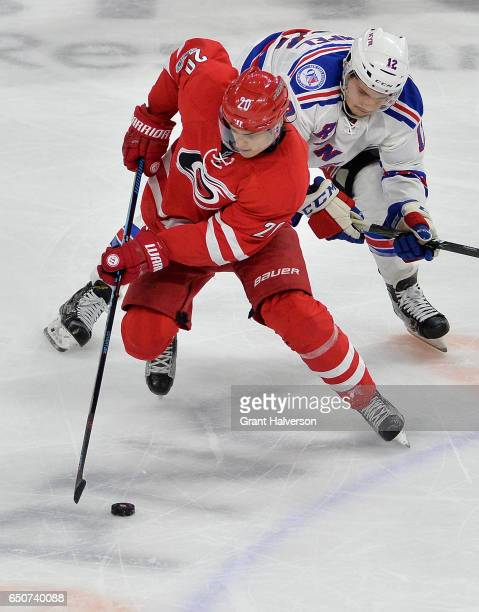 Sebastian Aho of the Carolina Hurricanes moves the puck against Matt Puempel of the New York Rangers during the game at PNC Arena on March 9 2017 in...