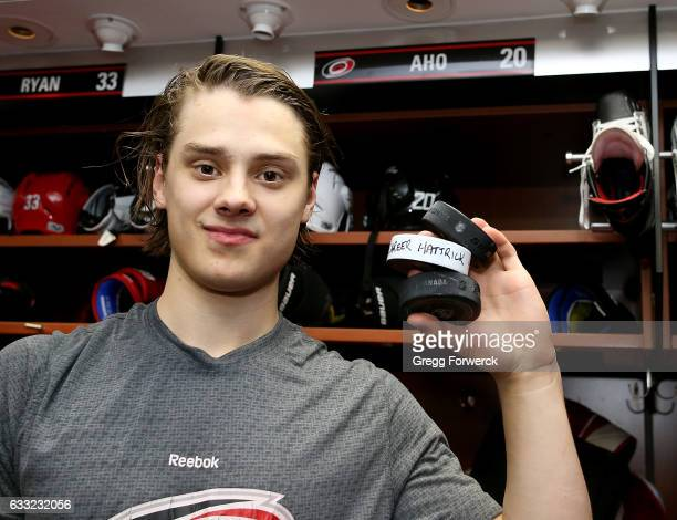 Sebastian Aho of the Carolina Hurricanes poses with three pucks celebrating his first career hat trick following an NHL game against the Philadelphia...