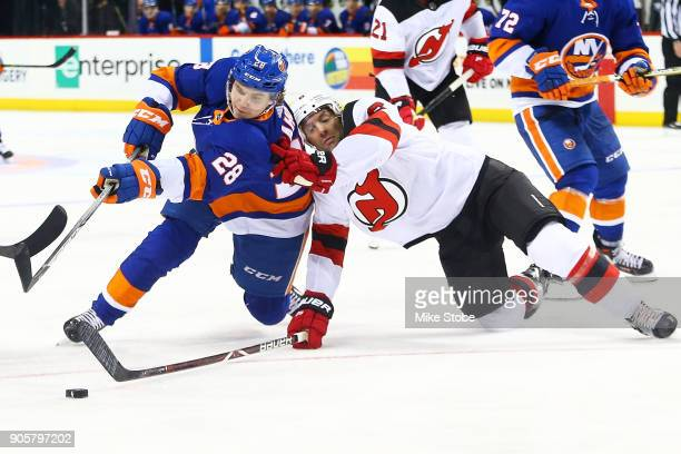 Sebastian Aho of the New York Islanders attempts to maintain control of the puck as he and defender Andy Greene of the New Jersey Devils fall to the...