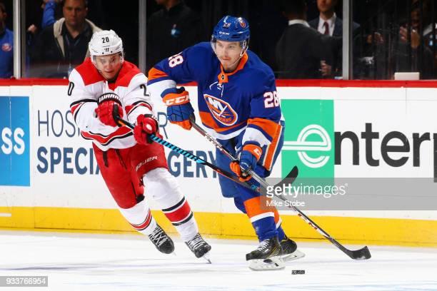 Sebastian Aho of the New York Islanders passes the puck amid pressure from Sebastian Aho of the Carolina Hurricanes during the third period at...