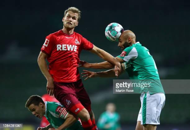 Sebastian Andersson of 1. FC Koeln competes for a header with Omer Toprak of SV Werder Bremen during the Bundesliga match between SV Werder Bremen...