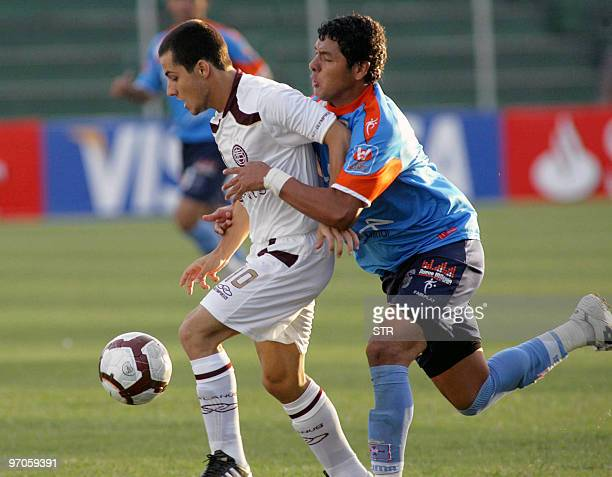 Sebastian Blanco of Argentinian Lanus vies for the ball with Omar Morales of Bolivian Blooming on February 25 during their Libertadores Cup group 4...