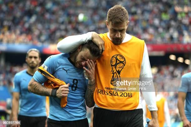 Sebastian Coates of Uruguay consoles teammate Nahitan Nandez of Uruguay following Uruguay's defeat during the 2018 FIFA World Cup Russia Quarter...