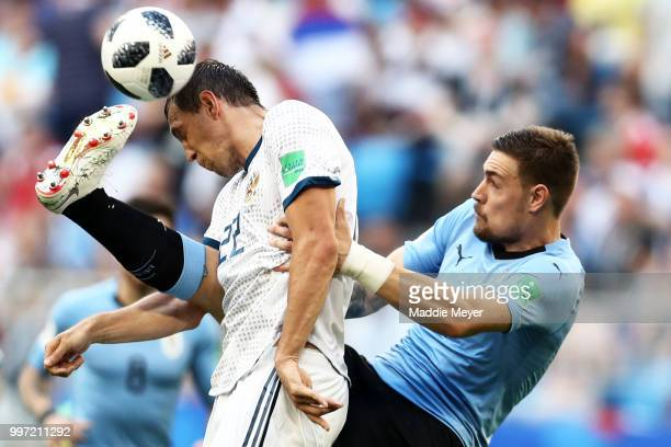 Sebastian Coates of Uruguay tackles Artem Dzyuba of Russia during the 2018 FIFA World Cup Russia group A match between Uruguay and Russia at Samara...