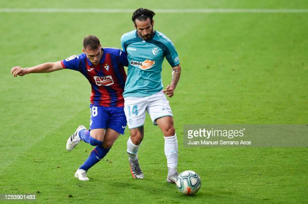 Sebastian Cristoforo of SD Eibar is challenged by Ruben Garcia of CA Osasuna during the Liga match between SD Eibar SAD and CA Osasuna at Ipurua...