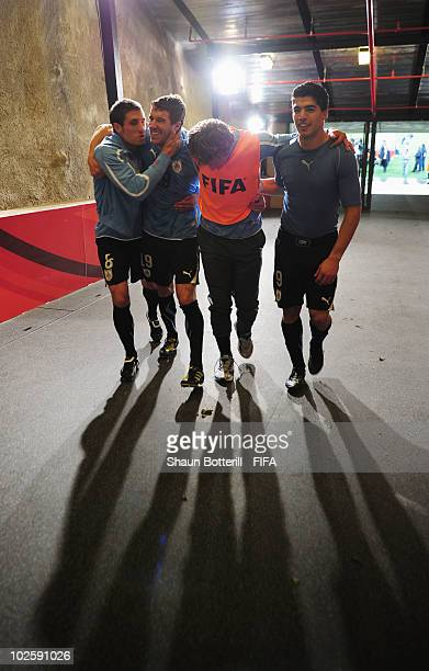 Sebastian Eguren Andres Scotti Diego Lugano and Luis Suarez of Uruguay celebrate winning the penalty shoot out and progress to the semi finals during...