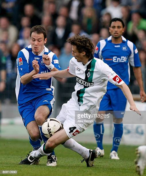Sebastian Freis of Karlsruhe is challenged by Roel Brouwers of Moenchengladbach during the Bundesliga match between Karlsruher SC and Borussia...