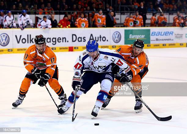 Sebastian Furchner and Kai Hospelt of Wolfsburg and Christoph Ullmann of Mannheim battle for the puck in game two of the DEL play-offs between...