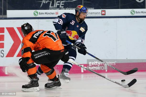 Sebastian Furchner of Grizzlys Wolfsburg vies Yannic Seidenberg of Red Bull Munich during the 49th game day of the German Ice Hockey League between...