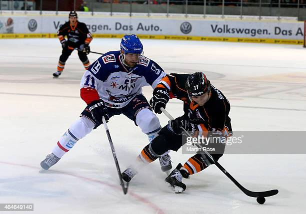 Sebastian Furchner of Wolfsburg and Andrew Joudrey of Mannheim battle for the puck during the DEL match between Grizzly Adams Wolfsburg and Adler...