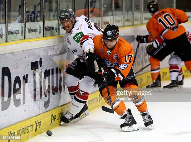 Sebastian Furchner of Wolfsburg and Corey Potter of Koeln battle for the puck during the DEL match between Grizzly Wolfsburg and Koelner Haie at...