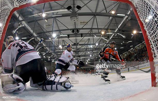 Sebastian Furchner of Wolfsburg and Richard Regehr of Muenchen battle for the puck in front of the net during the DEL match between Grizzly Adams...