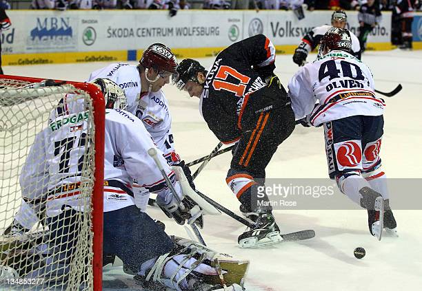 Sebastian Furchner of Wolfsburg and Stefan Ustorf and Darin Olver of Berlin battle for the puck during the DEL match between Grizzly Adams Wolfsburg...