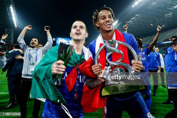 Sebastian Giovinco and Andre Carrillo Diaz of Al Hilal celebrate the champion with the trophy after the AFC Champions League Final second leg match...