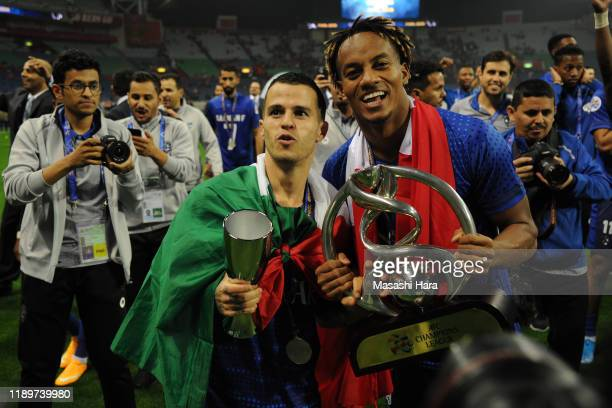 Sebastian Giovinco and Andre Diaz of Al Hilal hold the trophy after the AFC Champions League Final second leg match between Urawa Red Diamonds and Al...