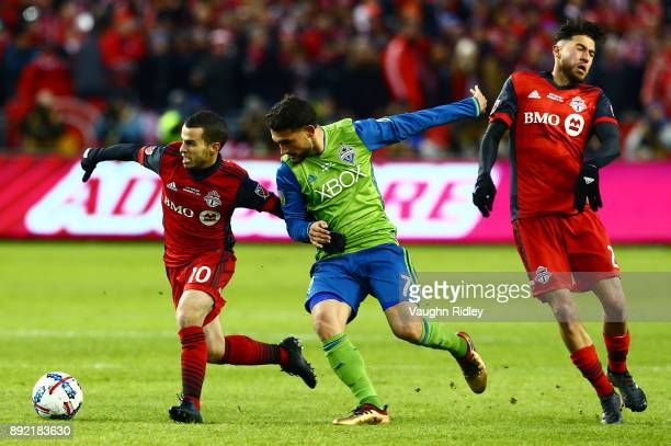Sebastian Giovinco and Jonathan Osorio of Toronto FC fight for the ball with Cristian Roldan of the Seattle Sounders during the first half of the...