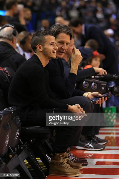 Sebastian Giovinco of Toronto FC and Brendan Shanahan President of the Toronto Maple Leafs watch from their court side seats during the first half of...