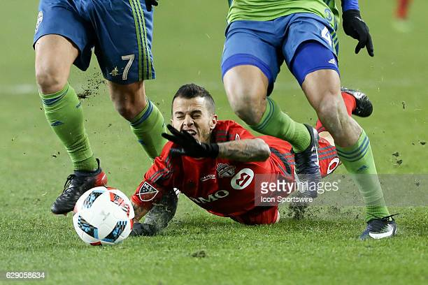 Sebastian Giovinco of Toronto FC battles for the ball against Cristian Roldan and Tyrone Mears of Seattle Sounders during the MLS Cup Finals of the...