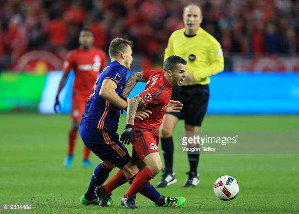 Sebastian Giovinco of Toronto FC battles for the ball with Frederic Brillant of New York City FC during the first half of an MLS Conference semifinal...
