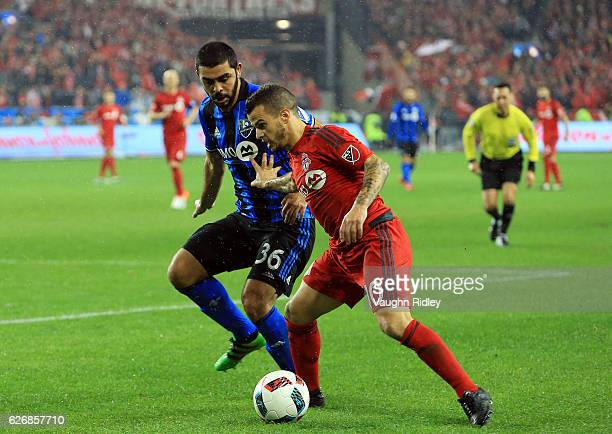 Sebastian Giovinco of Toronto FC battles for the ball with Vctor Cabrera of Montreal Impact during the first half of the MLS Eastern Conference Final...