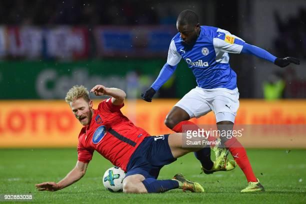 Sebastian Griesbeck of Heidenheim is challenged by David Kinsombi of Kiel during the Second Bundesliga match between Holstein Kiel and 1 FC...