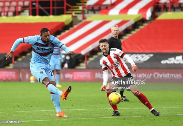 Sebastian Haller of West Ham United scores their sides first goal whilst under pressure from Ollie Norwood of Sheffield United during the Premier...