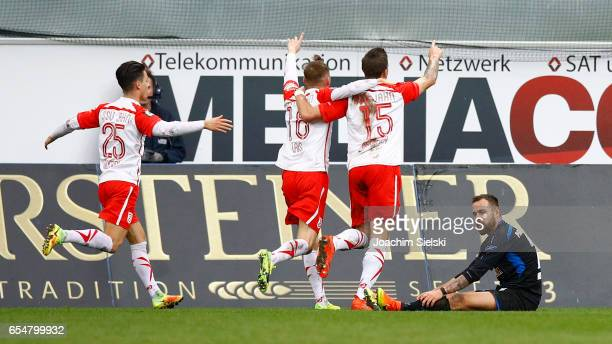 Sebastian Heidinger of Paderborn Erik Thommy Marc Lais and Marco Gruettner of Regensburg celebrate the Goal 01 during the third league match between...