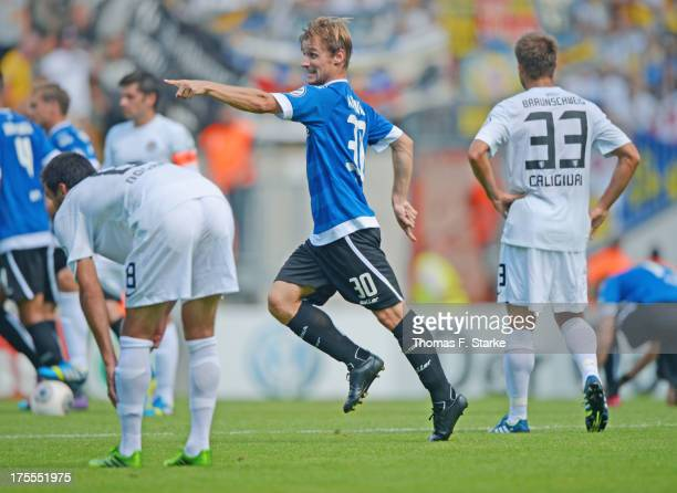 Sebastian Hille of Bielefeld celebrates scoring his teams first goal while Deniz Dogan and Marco Caligiuri of Braunschweig look dejected during the...