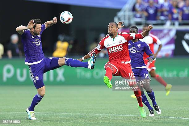 Sebastian Hines of Orlando City SC and Teal Bunbury of New England Revolution fight for a loose ball during a MLS soccer match at Camping World...