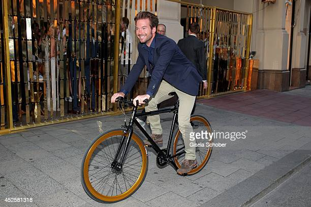 Sebastian Hoeffner rides his bike at the Eclat Dore summer party at Hotel Vier Jahreszeiten Kempinski on July 23 2014 in Munich Germany