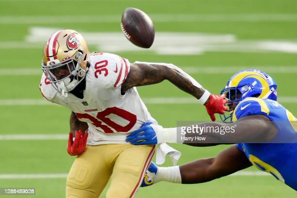 Sebastian Joseph-Day of the Los Angeles Rams forces a fumble by Jeff Wilson Jr. #30 of the San Francisco 49ers during the first quarter at SoFi...