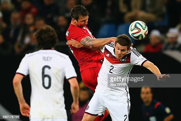 Sebastian Jung of Germany jumps for a header with Jakub Wawrzyniak of Poland during the international friendly match between Germany and Poland at...