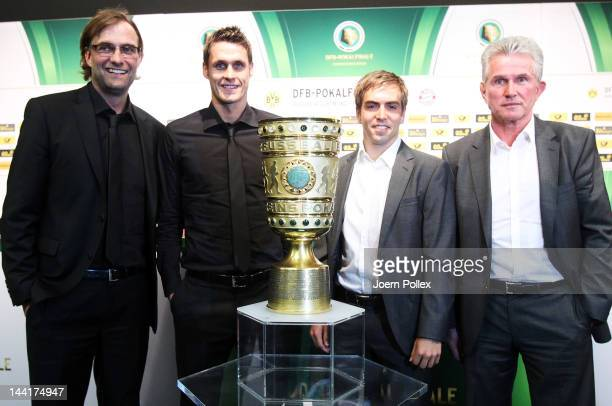 Sebastian Kehl and head coach Juergen Klopp of Dortmund and head coach Jupp Heynckes and Philipp Lahm of Muenchen are pictured with the cup after the...