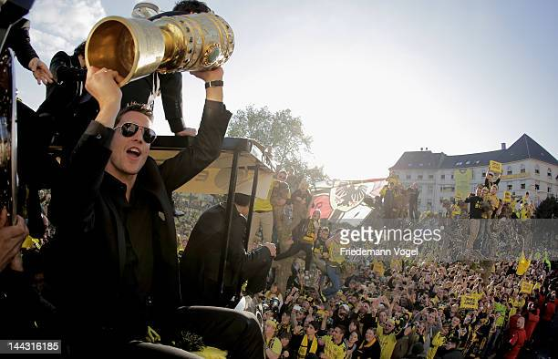 Sebastian Kehl of Borussia Dortmund celebrates with the DFB Cup during a victory parade on an open top bus after winning the DFB Cup and Bundesliga...
