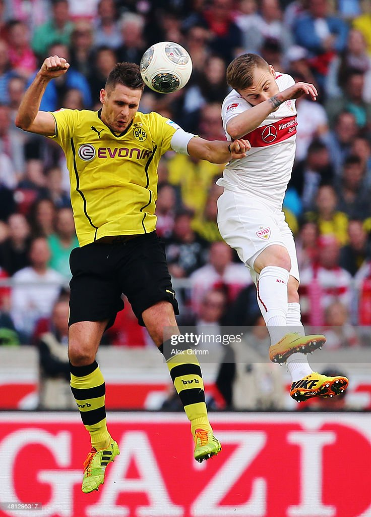 Sebastian Kehl (L) of Dortmund jumps for a header with Alexandru Maxim of Stuttgart during the Bundesliga match between VfB Stuttgart and Borussia Dortmund at Mercedes-Benz Arena on March 29, 2014 in Stuttgart, Germany.