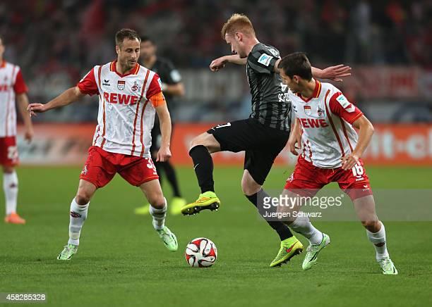Sebastian Kerk of Freiburg tackles Matthias Lehmann of Cologne and Pawel Olkowski during the Bundesliga match between 1. FC Koeln and SC Freiburg at...