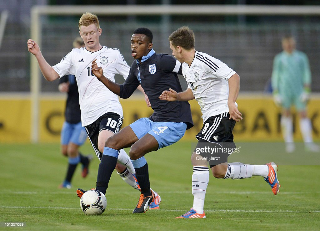 Sebastian Kerk (L) of Germany and Nathaniel Chalobah (C) of England battle for the ball during the Under 19 international friendly match between Germany and England at Stadion an der Lohmuehle on September 6, 2012 in Luebeck, Germany.
