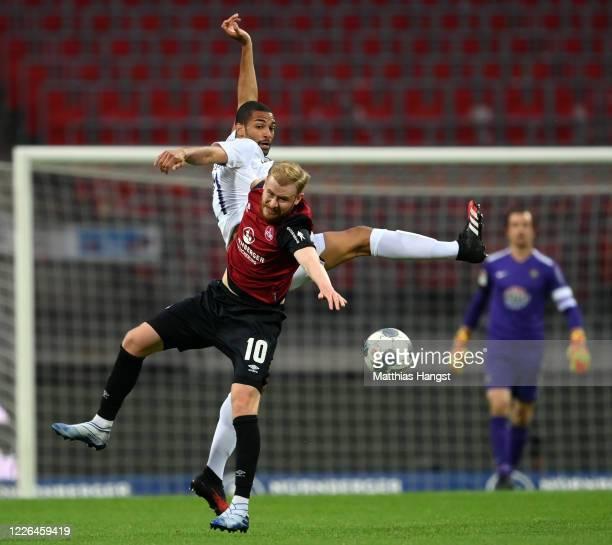 Sebastian Kerk of Nuernberg is challenged by Louis Samson of Aue during the Second Bundesliga match between 1. FC Nürnberg and FC Erzgebirge Aue at...