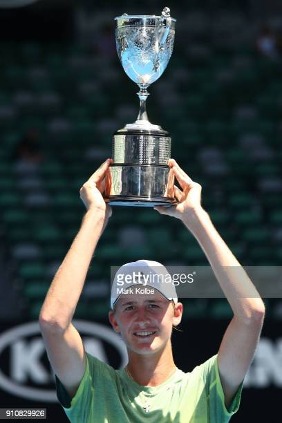 Sebastian Korda of the United States poses with the championship trophy after winning his Junior Boys' Singles Final against Chun Hsin Tseng of...