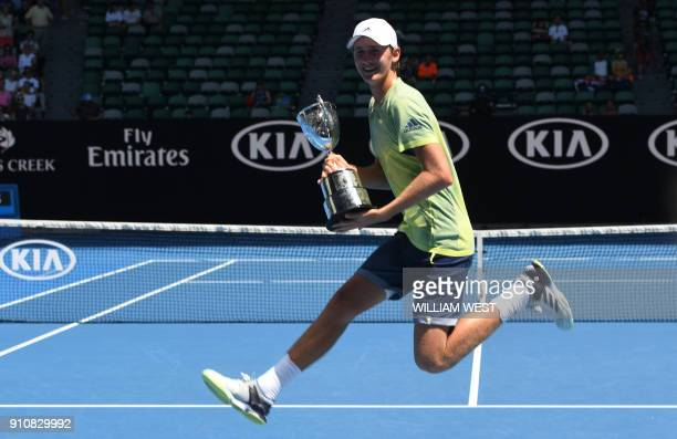 Sebastian Korda of the US poses with the winner's trophy after beating Taiwan's Tseng Chun Hsin in their junior boys' singles final match on day 13...