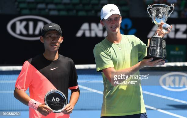 Sebastian Korda of the US poses with the winner's trophy beside Taiwan's Tseng Chun Hsin after their junior boys' singles final match on day 13 of...